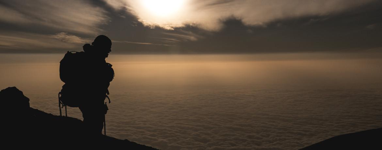 Maximo durante o amanhecer no dia de cume do Kili, mar de nuvens abaixo