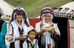 Kyrgyz_women_and_child_offering_bread_and_salt